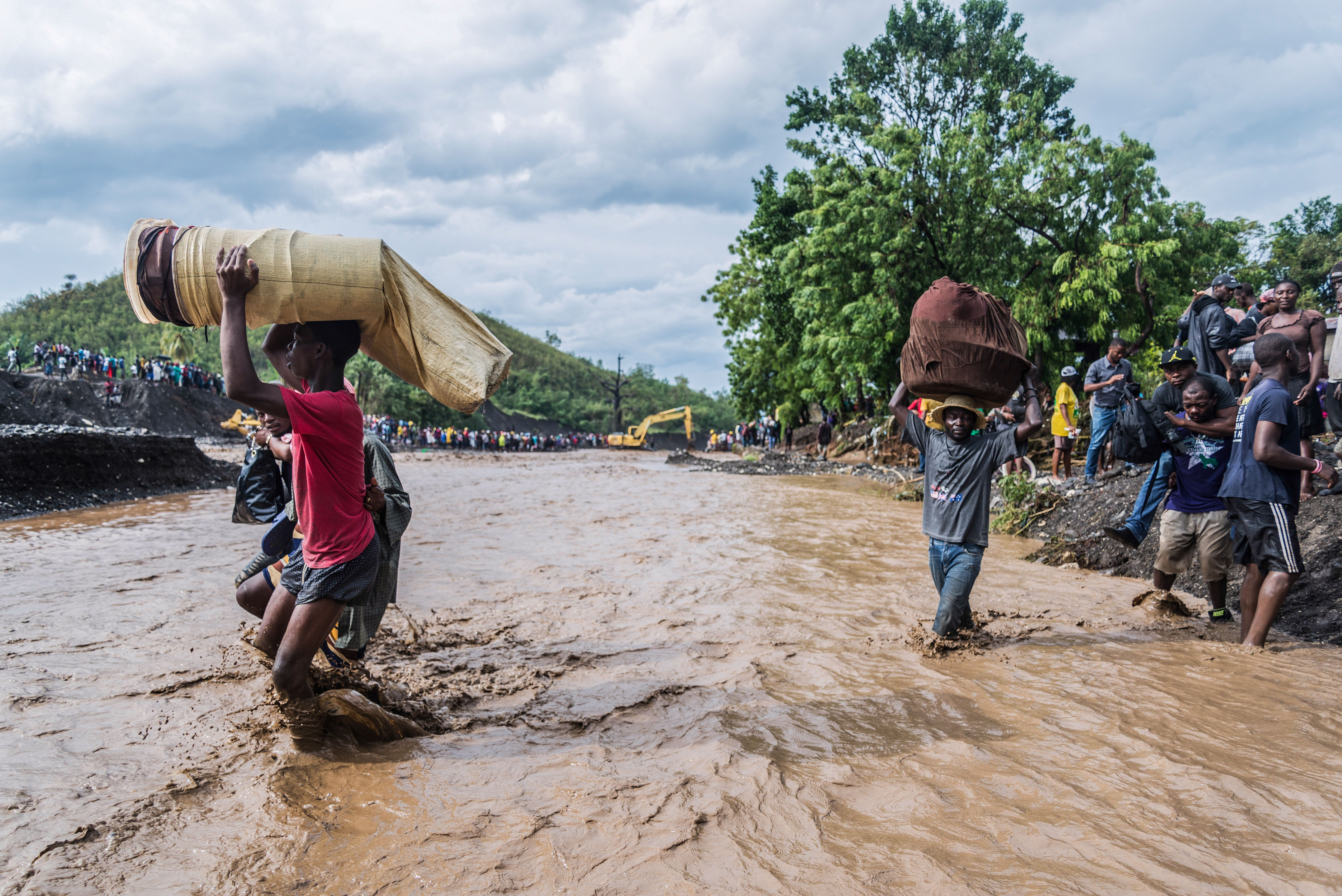 "October 5th, 2016: A bridge collapse in Petit Goave, Haiti forces residents to crossing the flooded ""ladigue"" river."