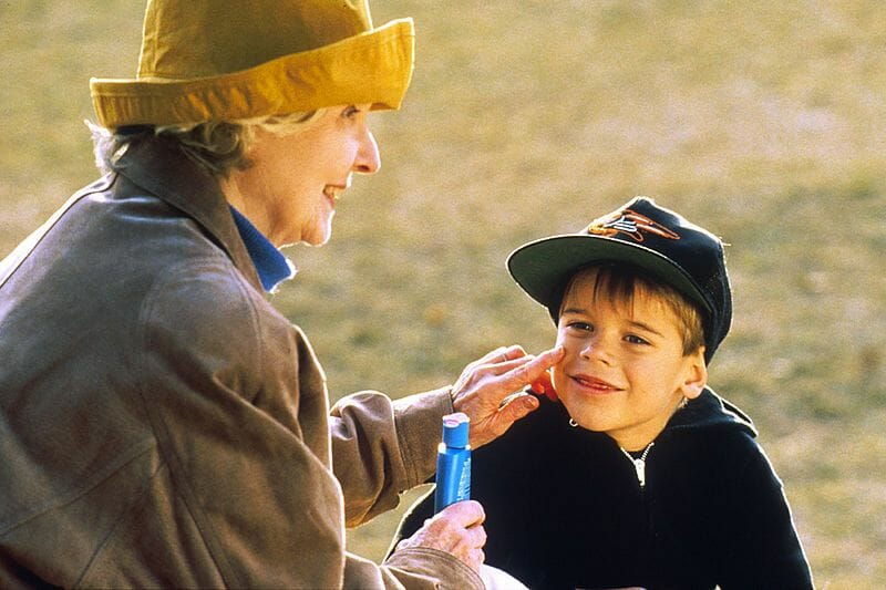 Older woman applying sunscreen to child's face.