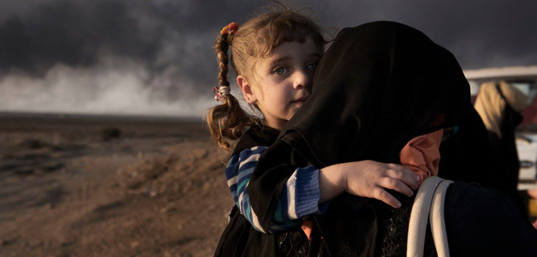 A newly displaced woman carries a child at a check point in Qayyara, south of Mosul. © UNICEF/UN040095/Romenzi (CNW Group/UNICEF Canada)
