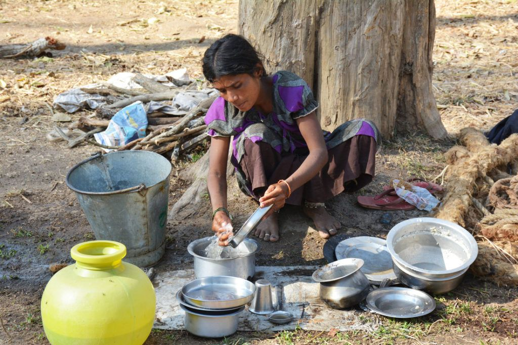A mahout woman washes the dishes without running water.