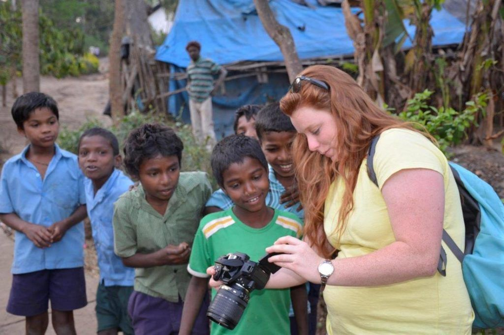 Student shows mahout children at an Indian elephant camp how to use a camera.