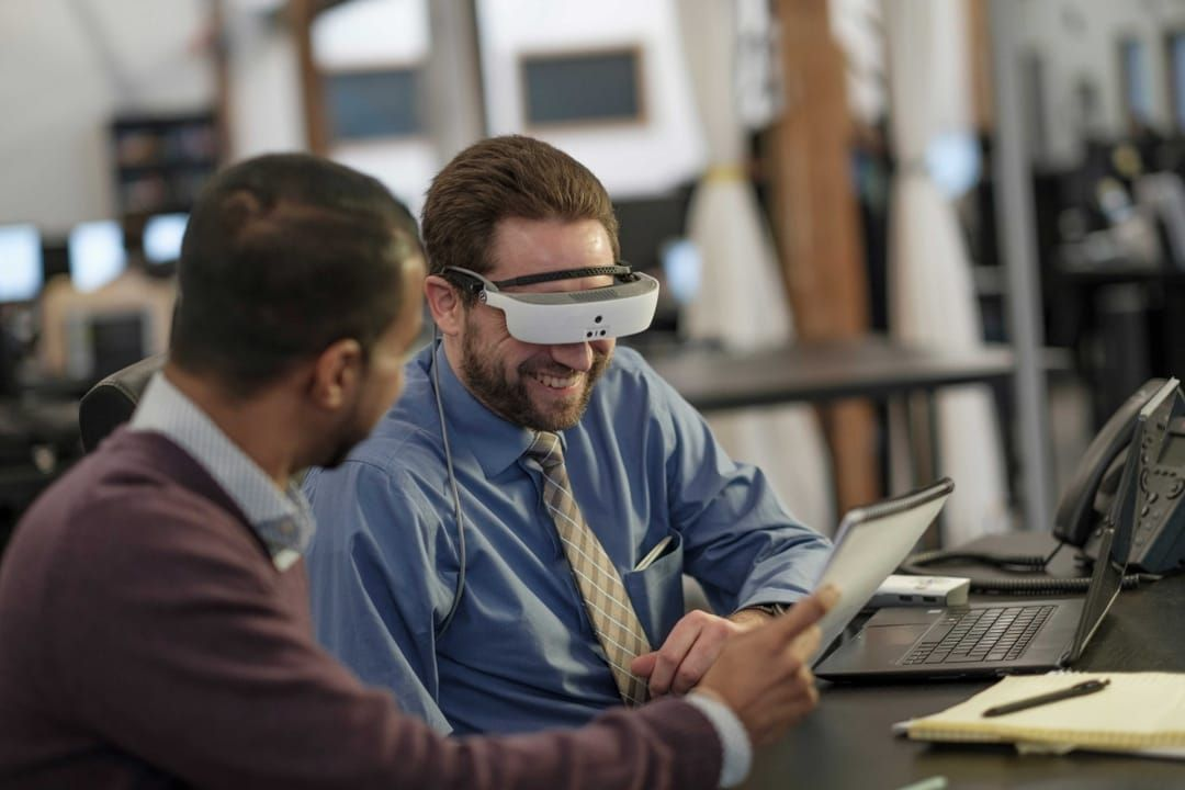 Two men look at a document while one of them tests out the new eSight wearable technology glasses