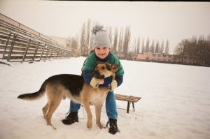 girl plays with alsatian puppy in the snow