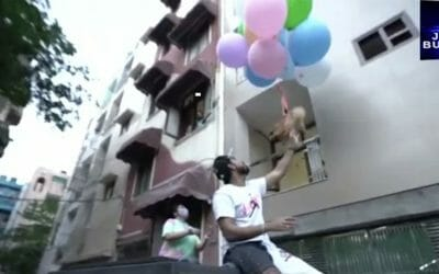 Man letting go of dog with balloons tied to back